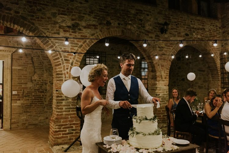 Bride and Groom Cutting the Three Tier Buttercream Wedding Cake with Olive Leaves Decor