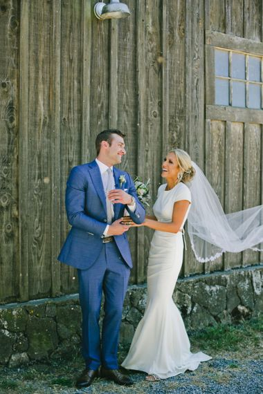 Groom in Blue Suit Supply Suit Turning Around to Greet His Bride  During First Look