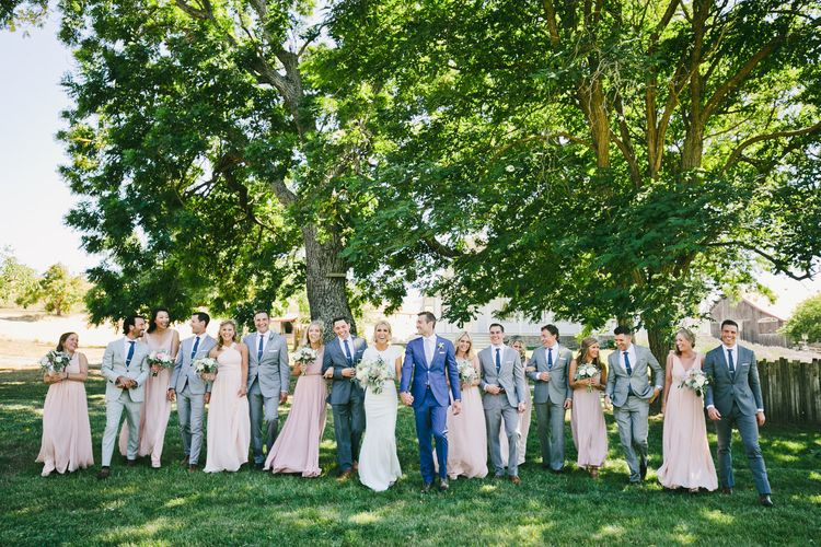 Wedding Party Portrait with Bridesmaids in Pink, Groomsmen in Grey and Groom in Blue Suit