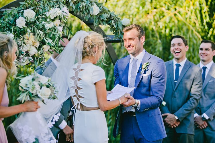 Outdoor Wedding Ceremony with Bride  in Fitted Noel and Jean Bridal Separates and Groom in Blue Suit Supply Suit