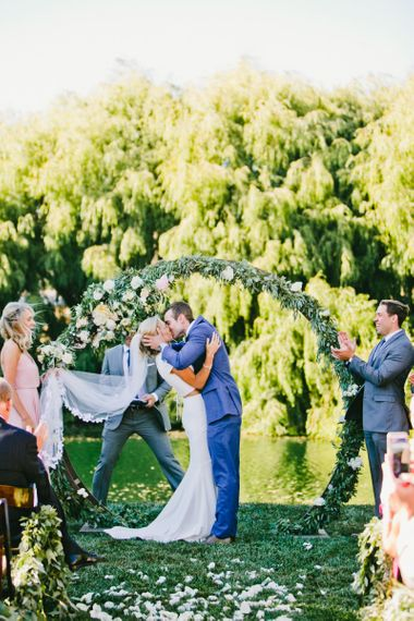 Bride in Fitted Noel and Jean Bridal Separates and Groom in Blue Suit Supply Suit Kissing in Front of Floral Moon Gate at Wedding Ceremony