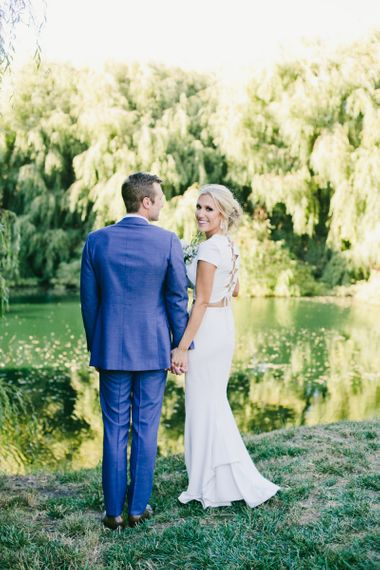 Bride in Fitted Noel and Jean Bridal Separates with Lace up Back Detail and Groom in Blue Suit Supply Suit