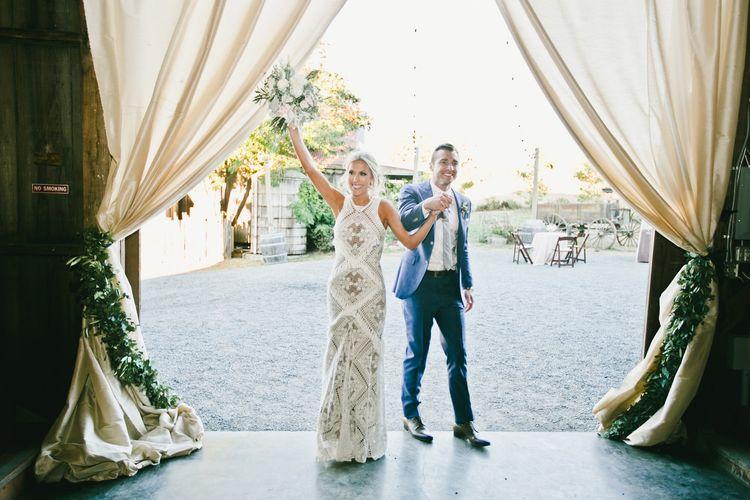Bride in Lace Rue De Seine Wedding Dress and Groom in Blue Suit Supply Suit