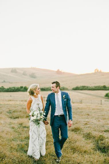Bride in Lace Rue De Seine Wedding Dress and Groom in Blue Suit Walking Through the Fields