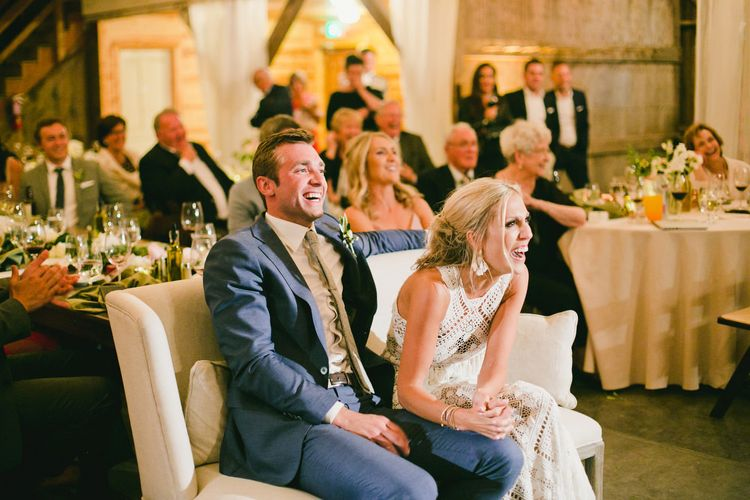 Bride in Lace Rue De Seine Wedding Dress and Groom in Blue Suit Laughing on Love Seat During Wedding Speeches