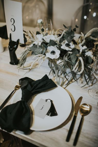 Gold Cutlery & Tassel Name Place Card | Elegant Tablescape with Ghost Chairs & Hanging Anemone Floral Arrangement | Minimalist Monochrome Inspiration with Anemone's & White Genista Flowers styled by The Bijou Bride | Igor Demba Photography | Gione da Silva  Film