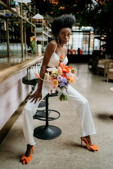 Stylish black bride in wedding trouser outfit holding a colourful Spring wedding flower bouquet