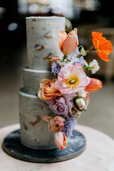 Three tier wedding cake decorated with spring wedding flowers