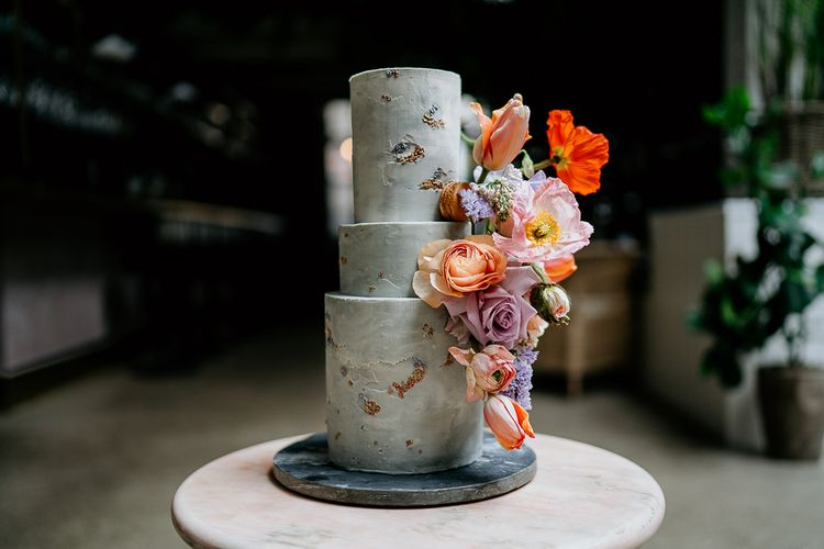 Modern marble wedding cake decorated with colourful  Spring wedding flowers
