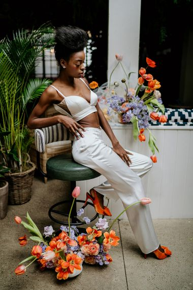 Stylish bride in crop top and trouser outfit with bright orange wedding shoes