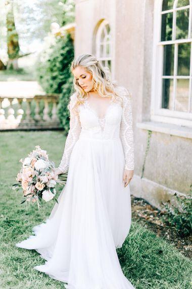 Bride in Romantic Lace Long Sleeve Wedding Dress Holding Peach & Cream Bridal Bouquet