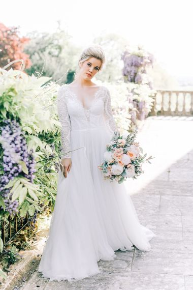 Bride in Lace and Tulle Wedding Dress Holding a Peach and White Wedding Bouquet