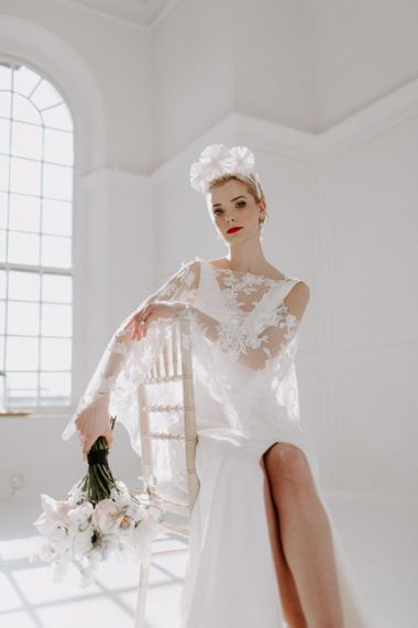modern wedding ideas with bride sitting on a chair  showing her front split wedding dress