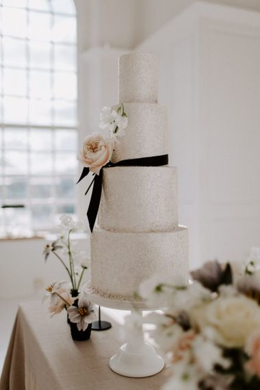 Four tier sparkly wedding cake with black ribbon