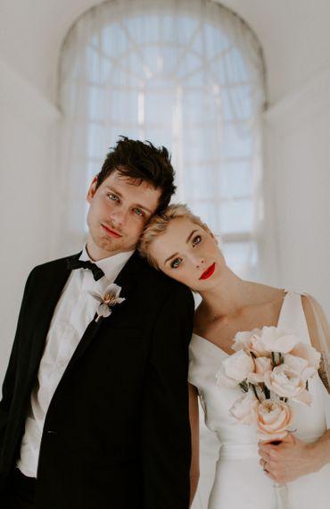 Bride and groom in black tie and modern wedding dress