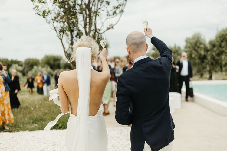 Bride and groom toast guests at Masseria Moroseta