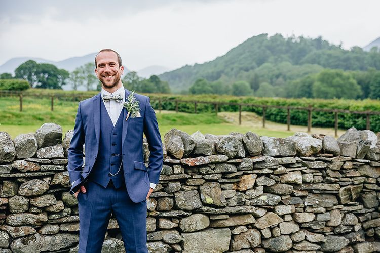Groom In Blue Suit With Floral Bow Tie From Moss Bros. // Image By Sarah Beth Photo
