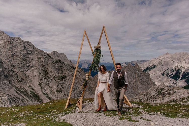 Bride and groom portrait in front of wooden frame altar at mountain wedding