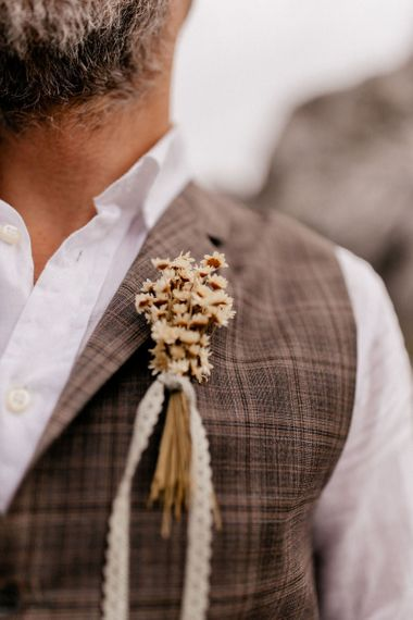 Dried flower button hole tied with lace ribbon
