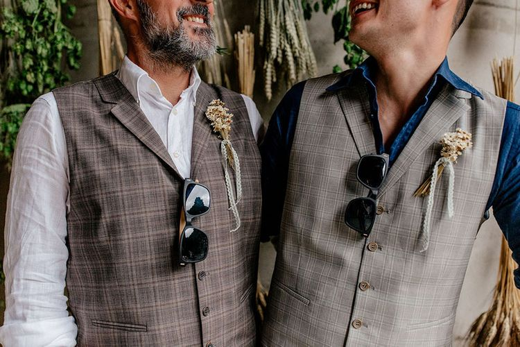 Groomsmen in check waistcoats with dried flower buttonholes