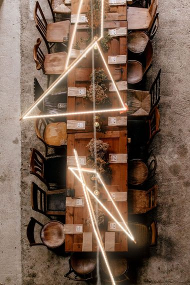 Ariel view of rustic tablescape with wooden chairs and table and light installation