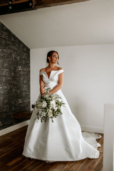 Bride in off the shoulder wedding dress with foliage and flower bouquet