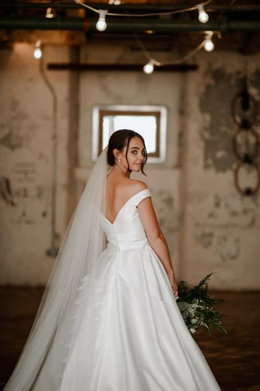 Off-the-shoulder wedding dress with bridal updo and veil