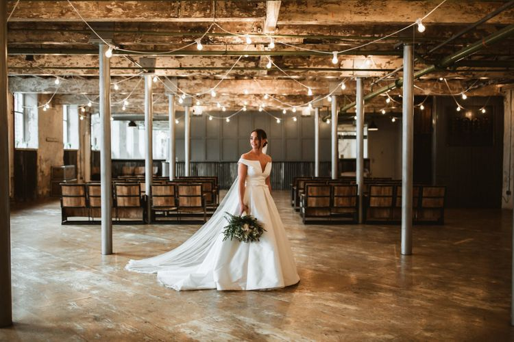 Industrial wedding with bride in off the shoulder wedding dress and cupcake wedding cake
