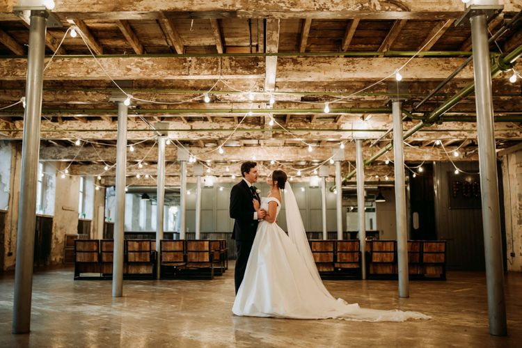Bride and groom under festoon lighting at industrial wedding with cupcake wedding cake
