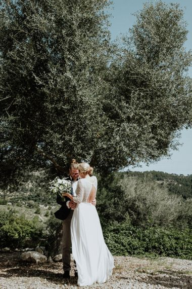 Bride and Groom Sharing their First Look with Bride in a Lace Back Rembo Styling Wedding Dress