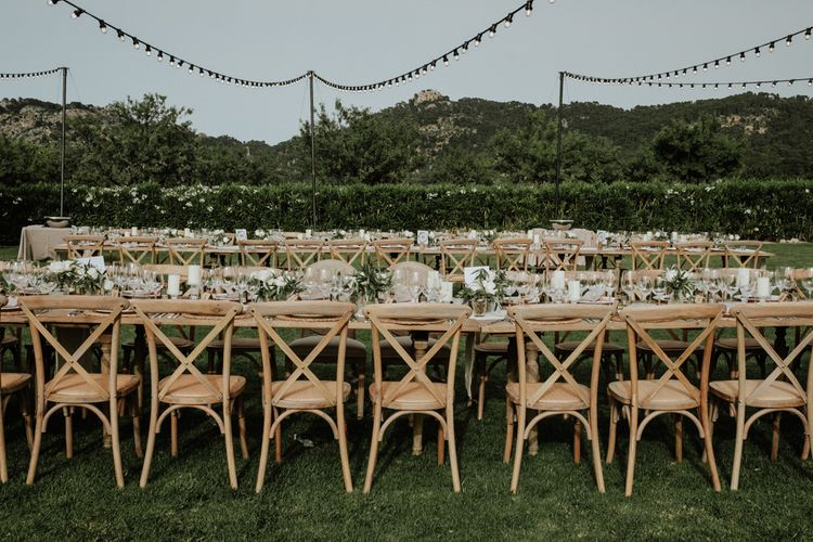 Outdoor Destination Wedding Reception with Wooden Table and Chairs and Festoon Lights
