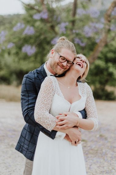 Bride in Rembo Styling Wedding Dress and Groom in Checked Blazer Embracing