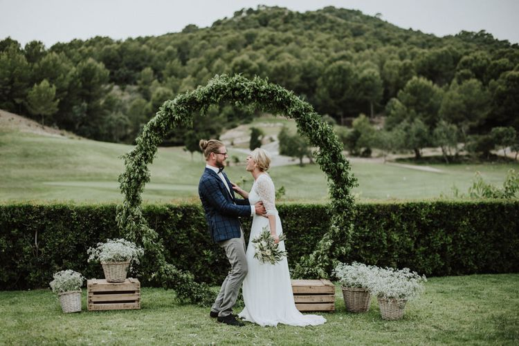Bride in Rembo Styling Wedding Dress and Groom  in Chino's and Checked Blazer Standing in Front of A Greenery Moon Gate