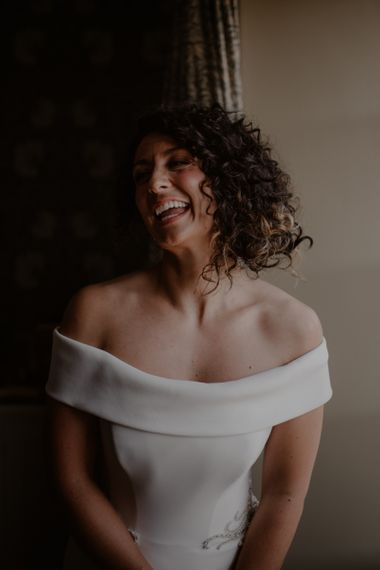 Bride with curly hair in off the shoulder wedding dress