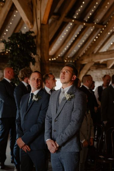 Groom in blue wool suit waiting at the altar
