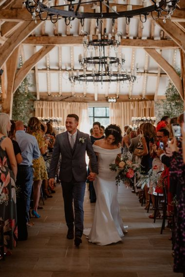 Bride in off the shoulder wedding dress and groom in blue suit walking up the aisle as husband and wife