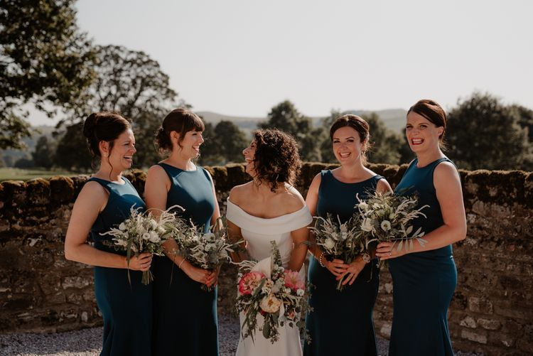 Bridesmaids in teal dresses and bride in Suzanne Neville wedding dress