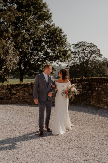 Bride in off the shoulder Suzanne Neville wedding dress and groom in grey wool suit