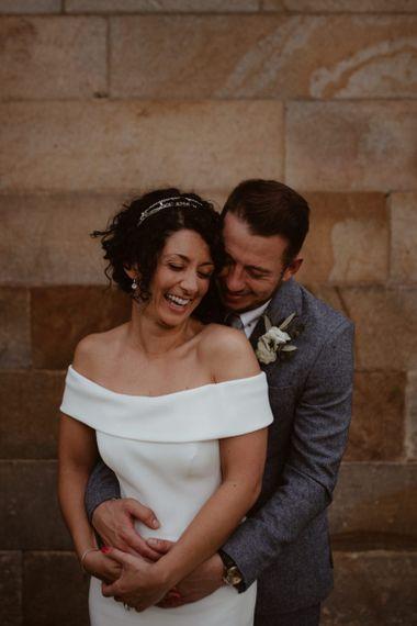 Groom in grey suit embracing his bride in off the shoulder wedding dress