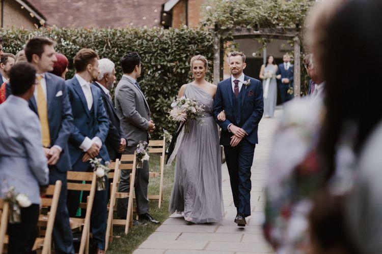 Bridesmaid in Grey Dress Walking Down Aisle With Groomsmen