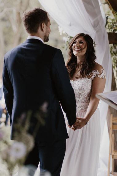 Bride with Capped Lace Sleeves Exchanging Vows with Husband