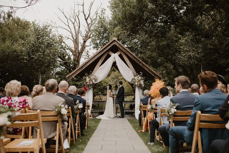 Outdoor Wedding Ceremony With Bride and Groom and Altar Decor
