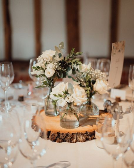 White wedding flower decor and rustic tree slice for Micklefield Hall wedding