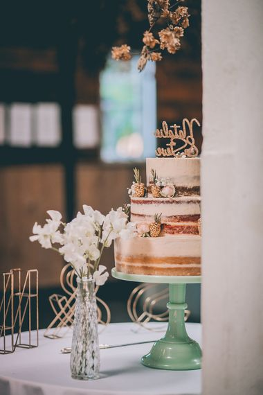 Semi Naked Wedding Cake Decorated with Pastel Flowers and Gold Painted Blackberries |  Pastel Green Cake Stand | Halterneck Maggie Sottero Dress and Garden Games at Gate Street Barn | Story + Colour Photography