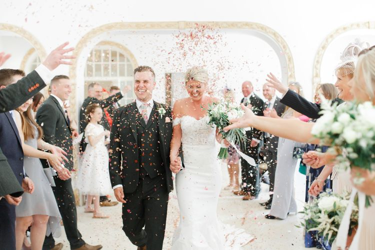 Confetti Moment with Bride in Lace St Patrick Wedding Dress and Groom in Grey Empire Outlet Suit