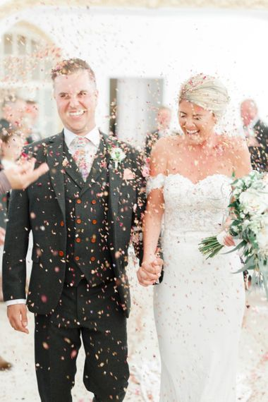 Confetti Exit with Bride in Lace St Patrick Wedding Dress and Groom in Grey Empire Outlet Suit