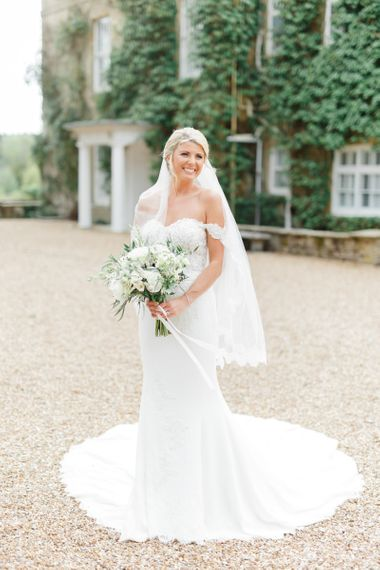 Beautiful Classic Bride in a Off the Shoulder St Patrick Wedding Dress Holding a Green and White Wedding Bouquet