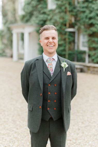 Groom in Three Piece Charcoal Grey Suit with Red Buttons