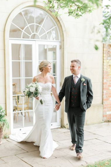 Bride and Groom Holding Hands in Front of the Orangery at Northbrook Park