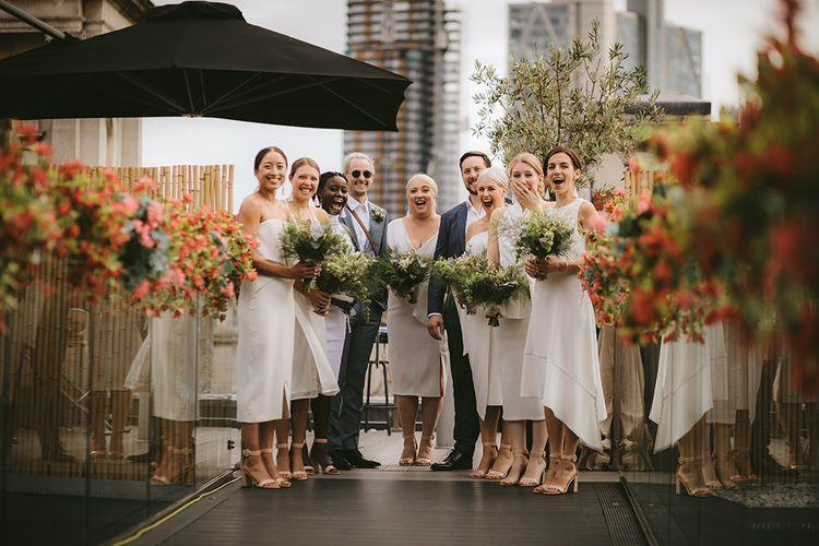 Bridal Party First Look | Bridesmaids in Mismatched White Dresses | Bridesmen in Blue Suits | Homemade Bouquets of White Flowers, Ferns and Foliage | Bike Shed Motorcycle Club Wedding for ELLE Digital Editor | Nigel John Photography